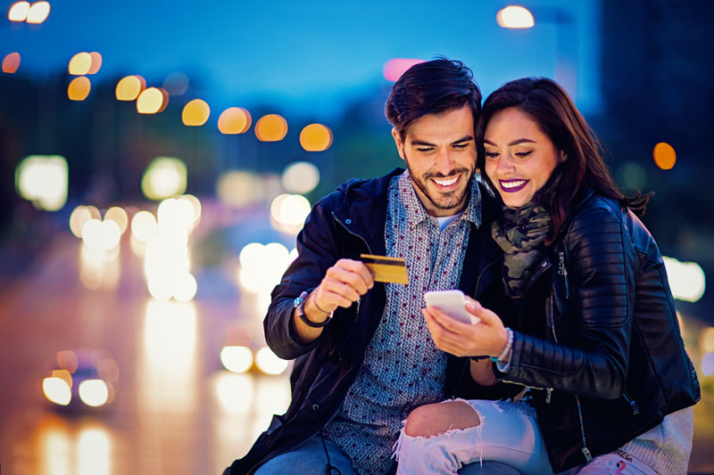 A couple looking at a credit card and their smart phone outside at night